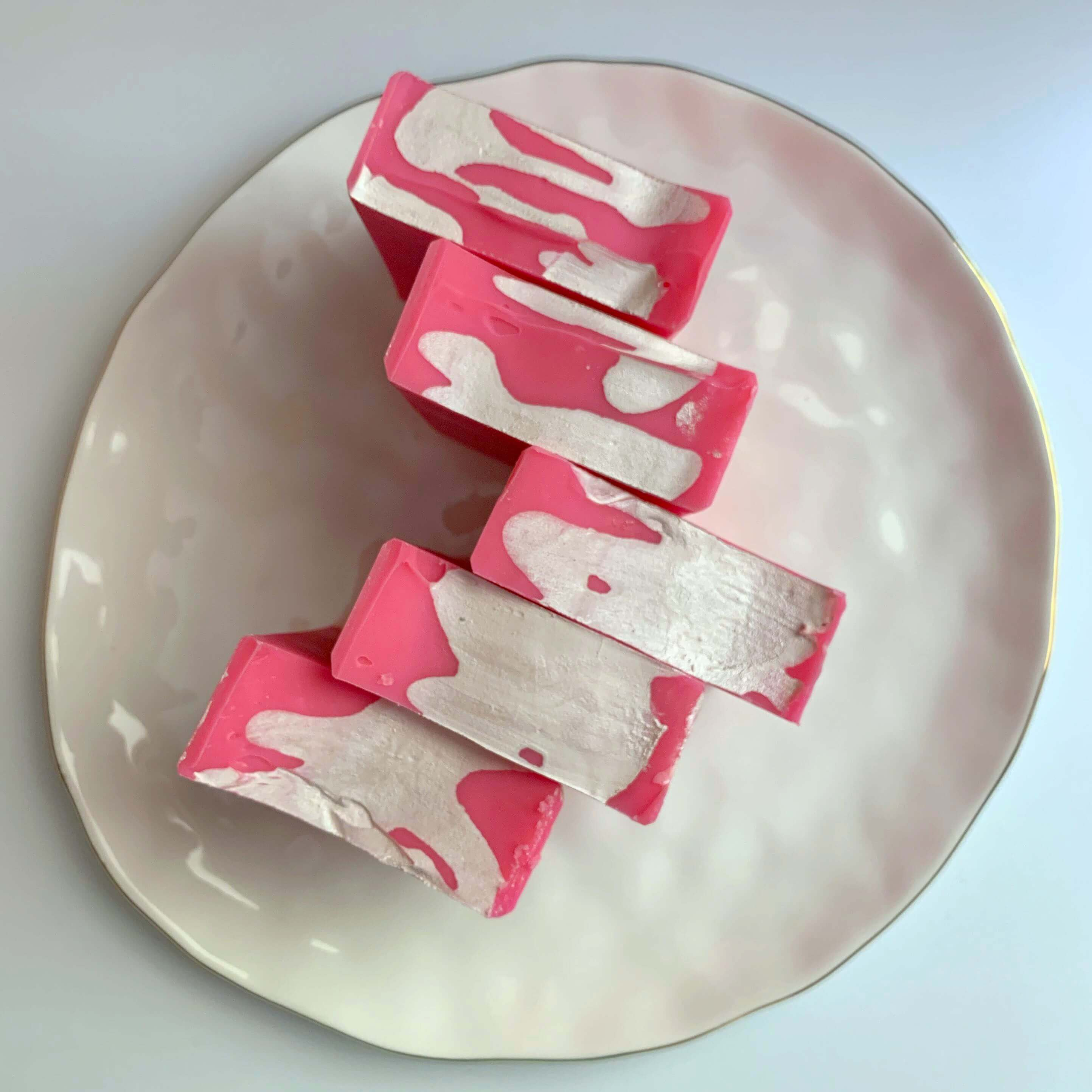 top down flat lay view of strawberry milkshake soaps on a white plate