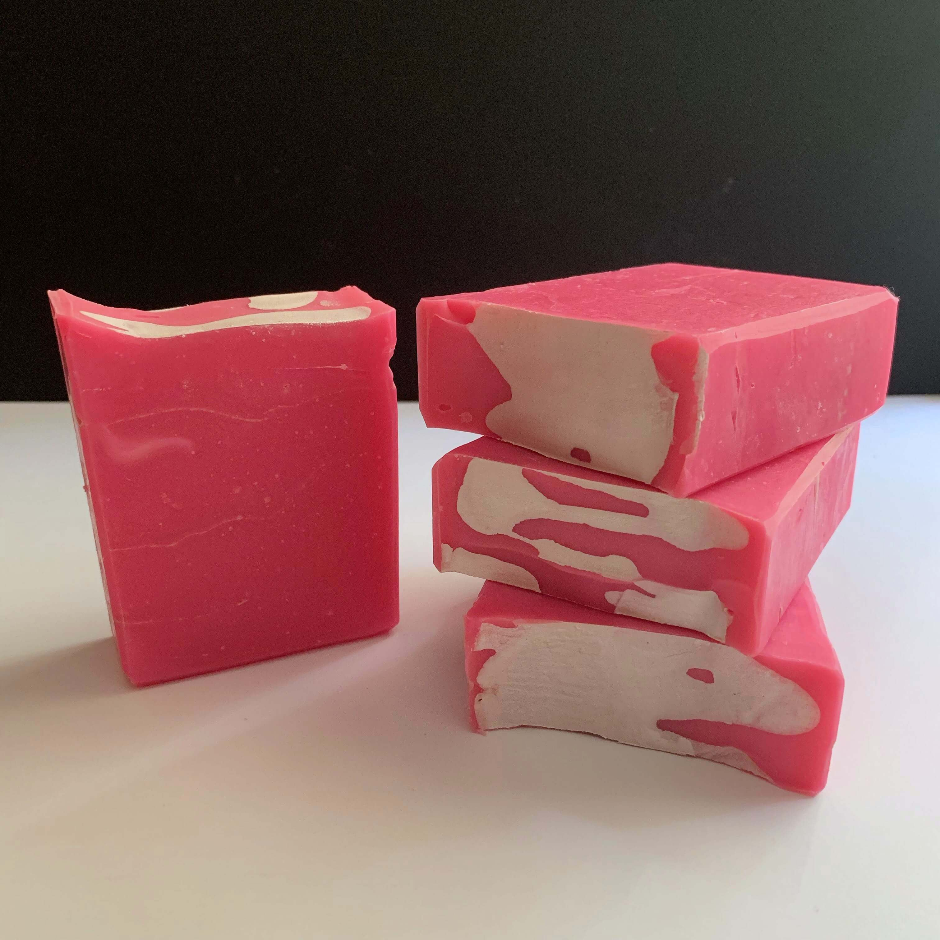 stack of handmade neon pink soap with strawberry milk fragrance by australian soap maker aliya hutchison