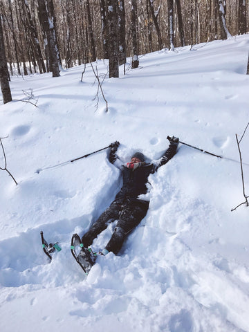 laying in the snow with snow shoes hiking