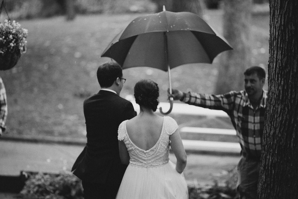 newly weds in the rain under umbrella on wedding day