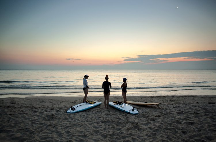 three women with surfboards on the beach sunrise