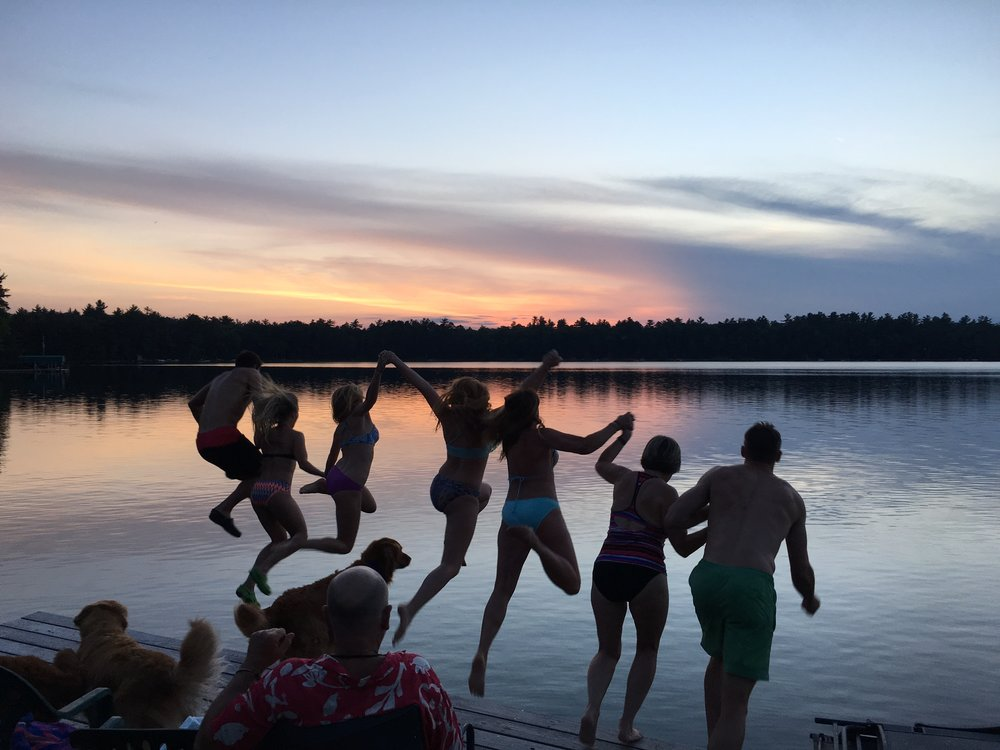 group jumping into the moon lake st germain wisconsin