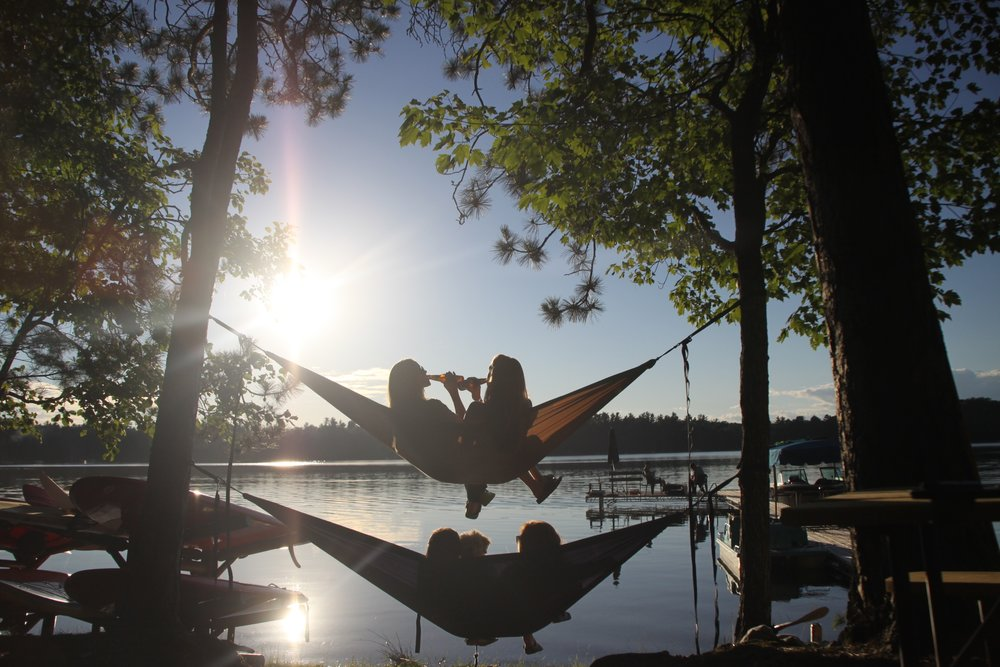 group of stacked hammocks having a drink watching the sunset over the lake