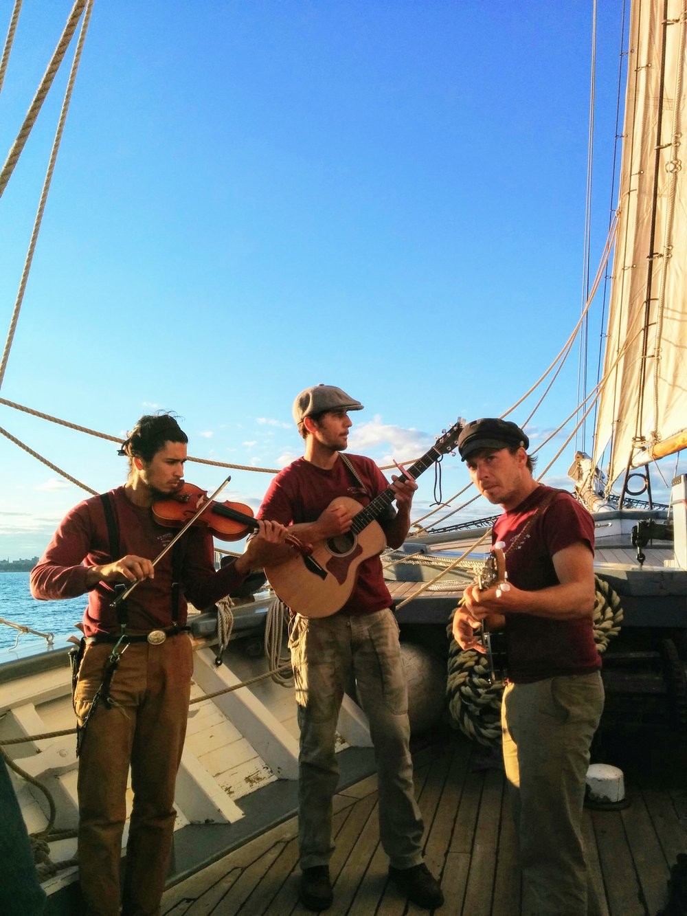 three man band playing on a boat