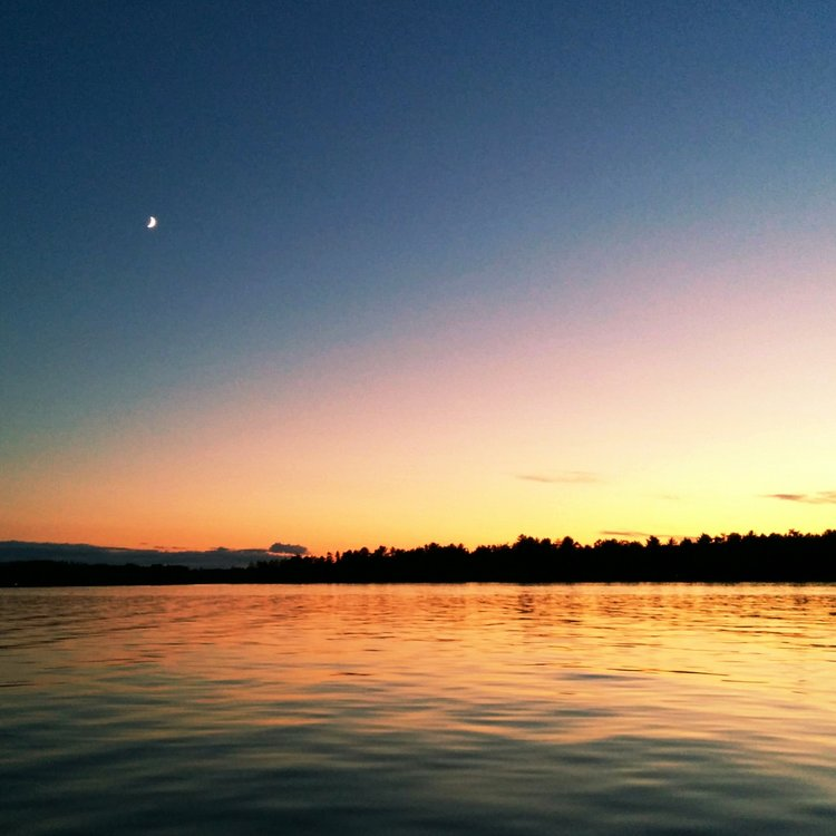 sunset with the moon out over the lake