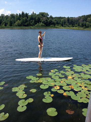 stand up paddle boarding among lily pads