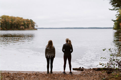 two women standing on the beach overlook the lake