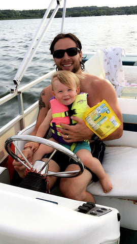 dad and kid driving the boat