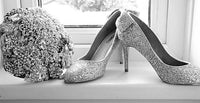 This is an image of a Sparkly Silver Wedding Bouquet display with a pair of Silver Jimmy Choo Shoes by Bridal Crystal Bouquets UK