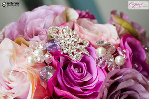This is a close up image of our lilac and pink artificial bouquet for a brides wedding with brooches.