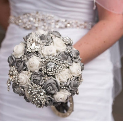 This is an image of a bride holding her Luxurious Silver Crystal Brooch Wedding Bouquet For A Traditional Wedding - Bridal Crystal Bouquets