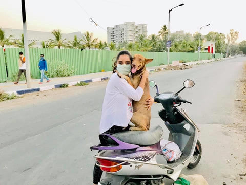 woman with dog on moped