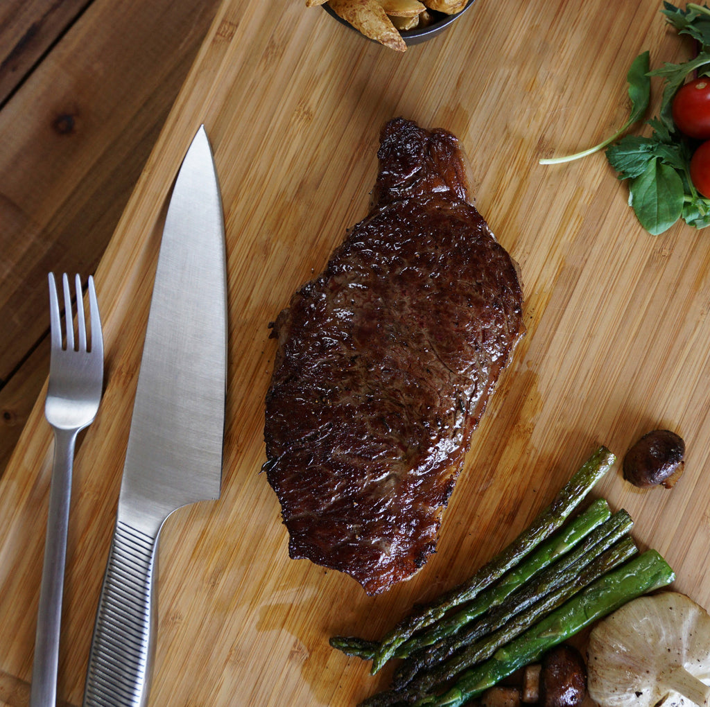 cooked steak on cutting board