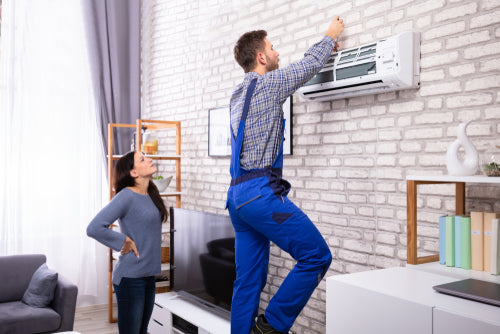 Young Woman Looking At Male Technician Repairing Air Conditioner