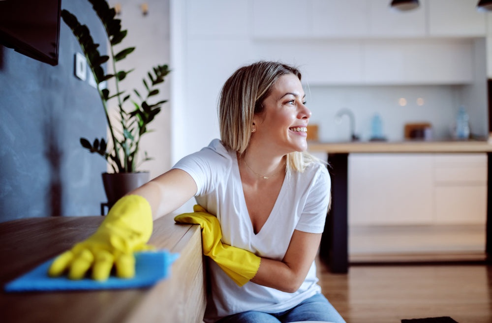 housewife with rubber gloves dusting shelf