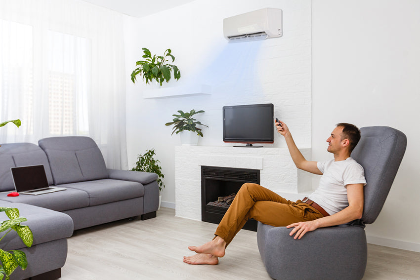 a man using a remote to turn on and adjust his air conditioner