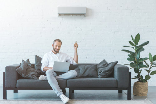 man turning on air conditioner with remote