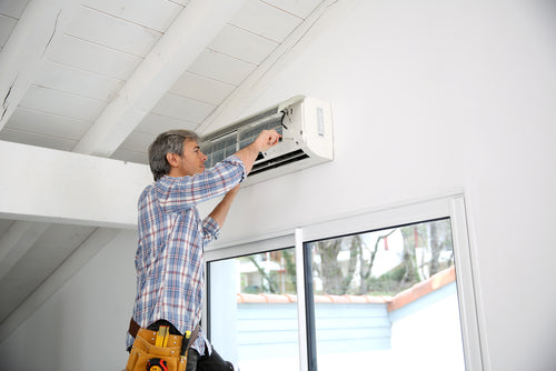 repairman fixing air conditioner