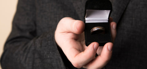 An image of a hand holding a ring box containing an Ebeniste wood ring.