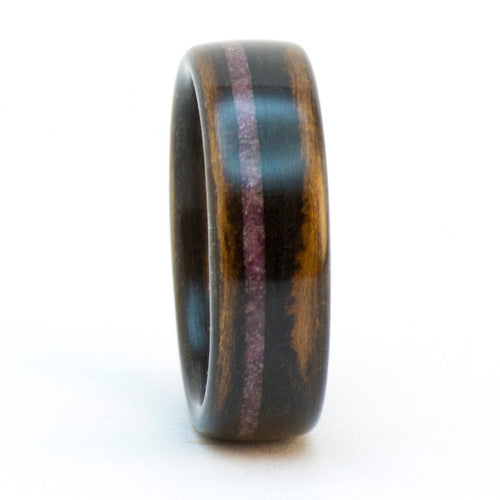 An ebony wood ring with a crushed ruby inlay.