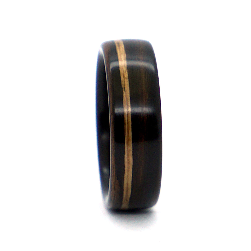 An ebony wood wedding ring with a whiskey barrel wood inlay, handcrafted by Ebeniste Wood Rings.