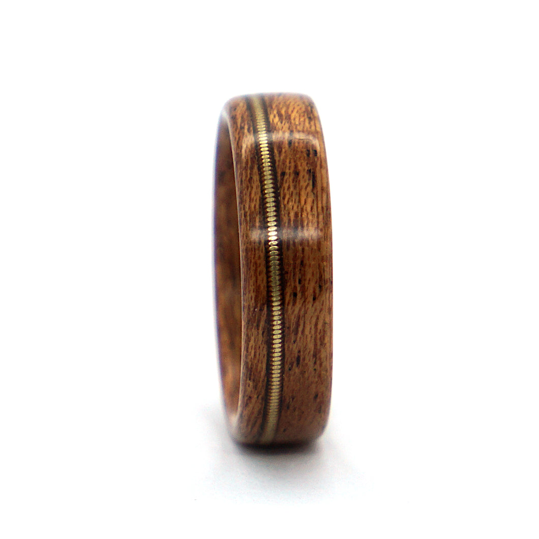 A mahogany wood wedding ring with a bronze acoustic guitar string inlay, handcrafted by Ebeniste Wood Rings.