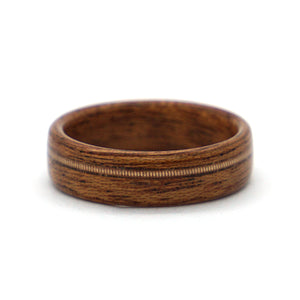 A mahogany wood wedding ring with a phosphor bronze acoustic guitar string inlay, handcrafted by Ebeniste Wood Rings.