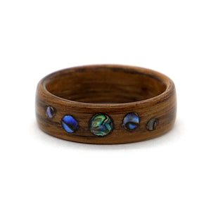 A brown oak wood ring with an inlaid pattern of abalone dots.