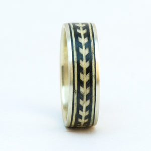 A sterling silver ring with wooden chevron banding.