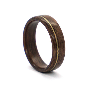 A walnut wood ring inlaid with a bronze acoustic guitar string by Ebeniste Wood Rings.