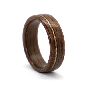 A walnut wood wedding ring with an acoustic guitar string inlay, handcrafted by Ébéniste Wood Rings.