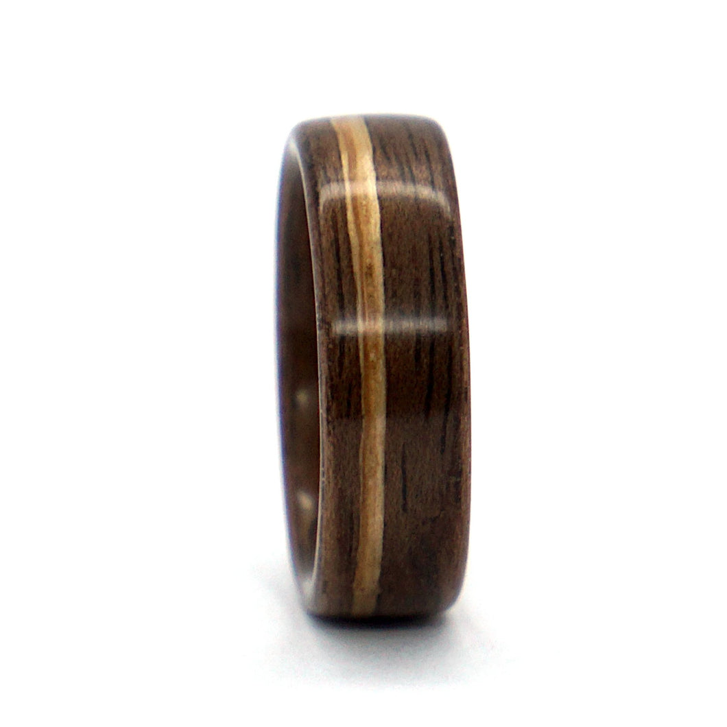 A walnut wood wedding ring with a whiskey barrel wood inlay, handcrafted by Ebeniste Wood Rings.
