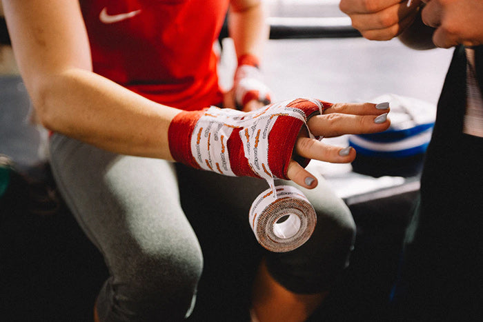 A female UFC fighter getting ready to fight wrapping boxing tape around her hands.