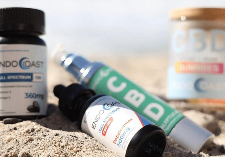 A selection of EndoCoast's high-quality CBD arranged in the beach sand.