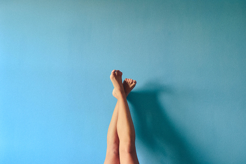 A woman's bare legs against a blue wall.