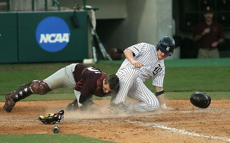 A baseball player sliding into a base as another player tags him out.