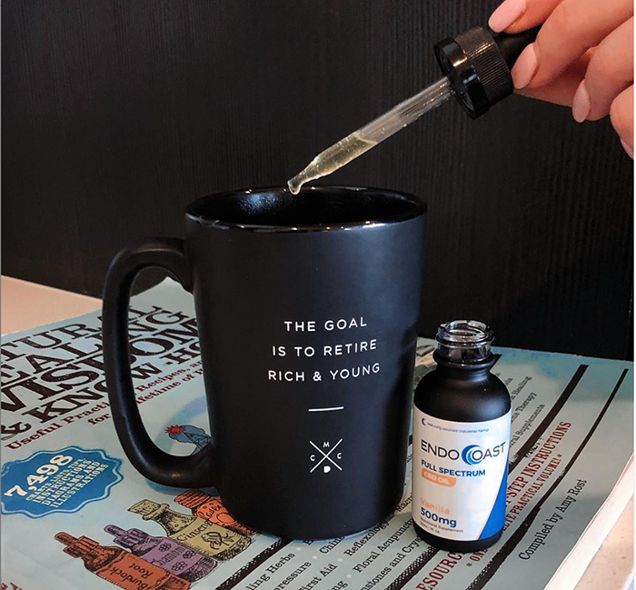 A bottle of EndoCoast's CBD oil next to a coffee mug.