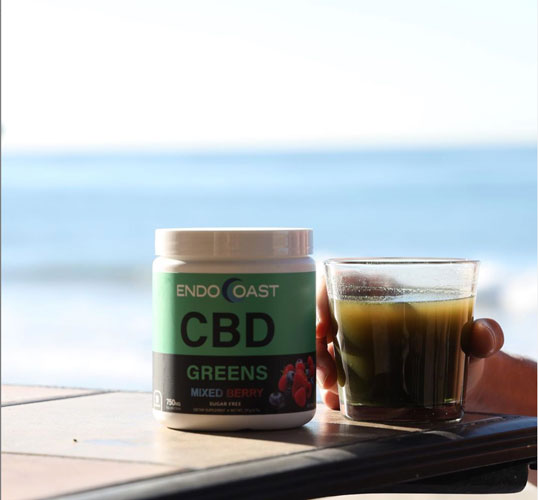 EndoCoast's high-quality CBD greens drink powder next to a glass.