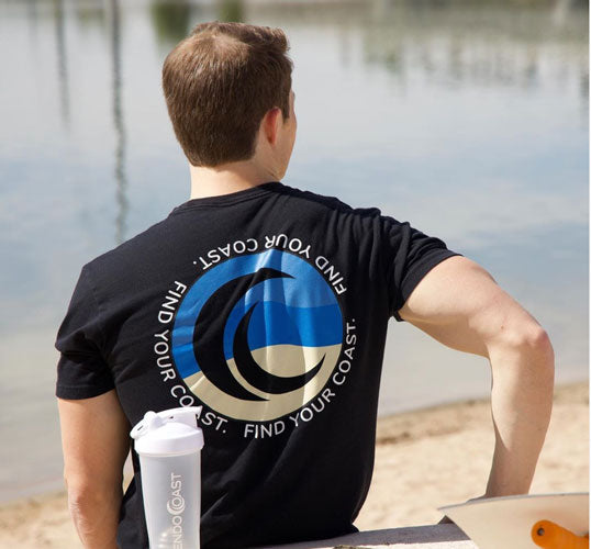 The back of a men's EndoCoast t-shirt on a model sitting by the water.