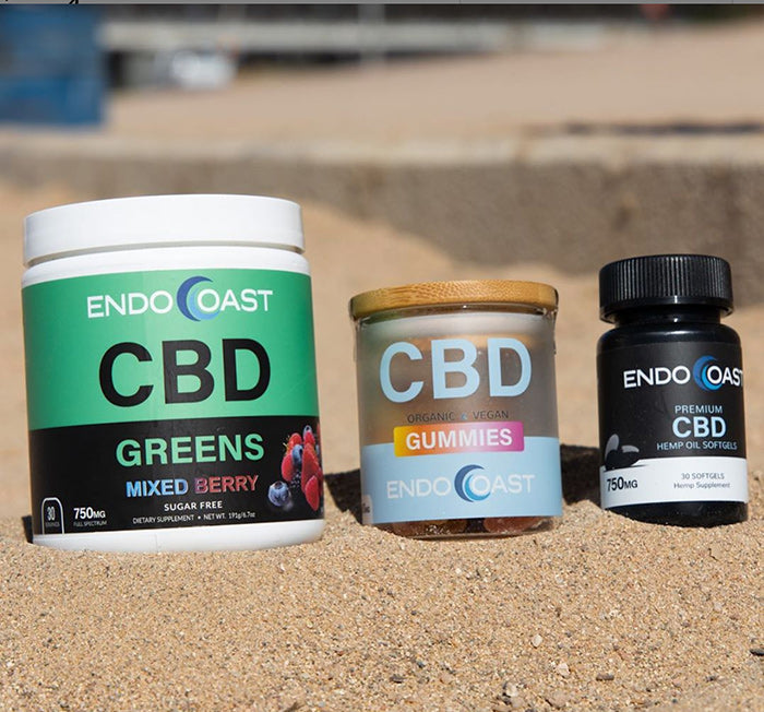 A collection of EndoCoast's high-quality CBD products posed on the sand.