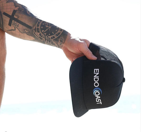 A model holds out an EndoCoast hat as an example of the best CBD oil brand for athletes.