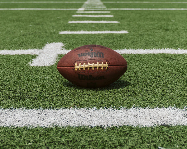 Leather football positioned on green turf