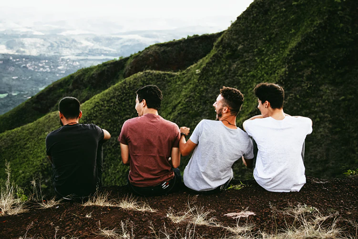 Four friends overlooking a mountain vista, finding their #Coast