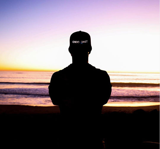 A man with an EndoCoast hat on stands by the ocean at sunset
