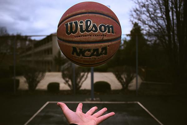 A Wilson and NCAA basketball with a hand below about to catch it