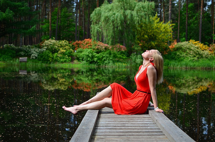 A woman in a red dress sitting on a pier