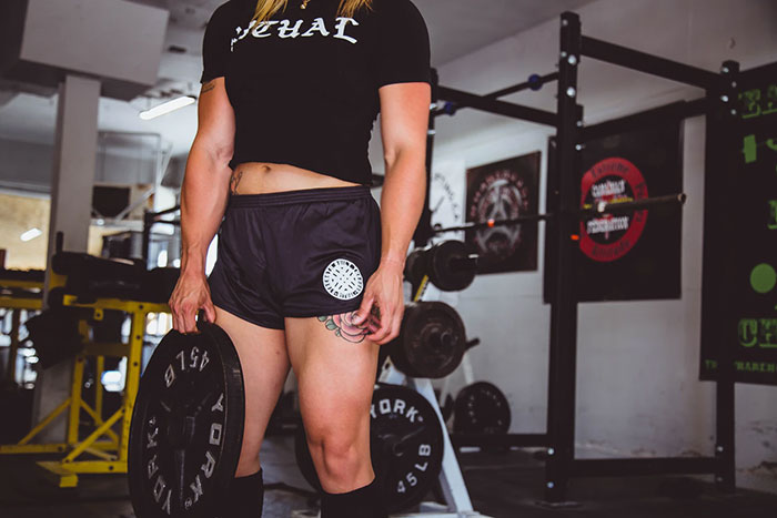 muscular woman wearing black workout outfit holding a 45 pound weight in a gym