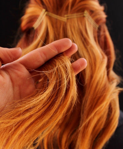picture of a hand running fingers through red hair to show save me from products help repair and protect hair