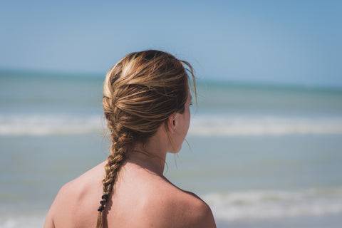 photo of woman's braided hair while she stands on the beach facing the ocean to show benefits of save me from sun and sweat reboot for hair