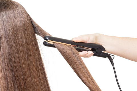 straightener being used on woman's hair to show what heat damage does to hair and the impact of heat protectants for protecting hair from heat damage